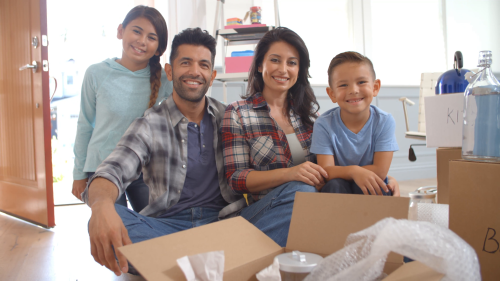 Portrait-of-hispanic-family-moving-into-new-home_rkxvk3hh__F0000