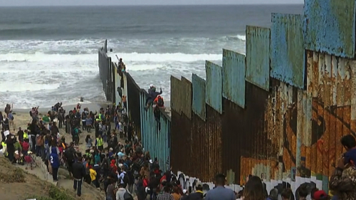 Immigrants-climbing-over-border-wall